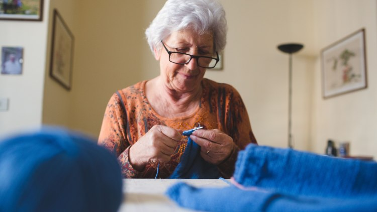 Elderly woman knitting in her home