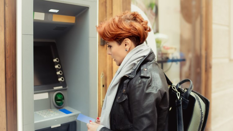 Business  woman withdrawing money from credit card at ATM