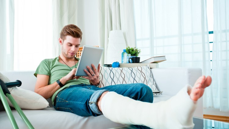 Young man with broken leg sitting on sofa at home and using digital tablet. , Young man with broken leg sitting on sofa at home and using digital tablet.